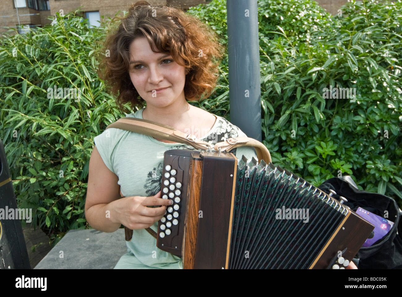 FEMALE STREET MUSICIAN PLAYING ACCORDION - Stock Image