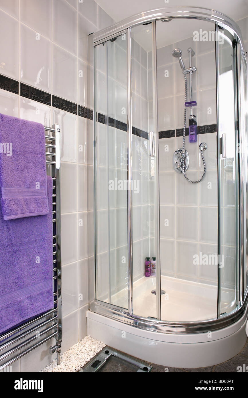 Corner shower cabinet with glass doors in modern grey tiled bathroom ...