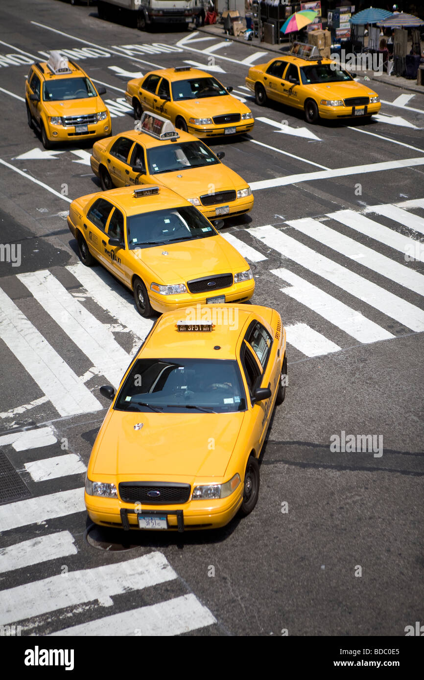 Six yellow cabs or taxi turn on Broadway and cross a pedestrian walkway as they arrive by a sunny day on Time Square - Stock Image