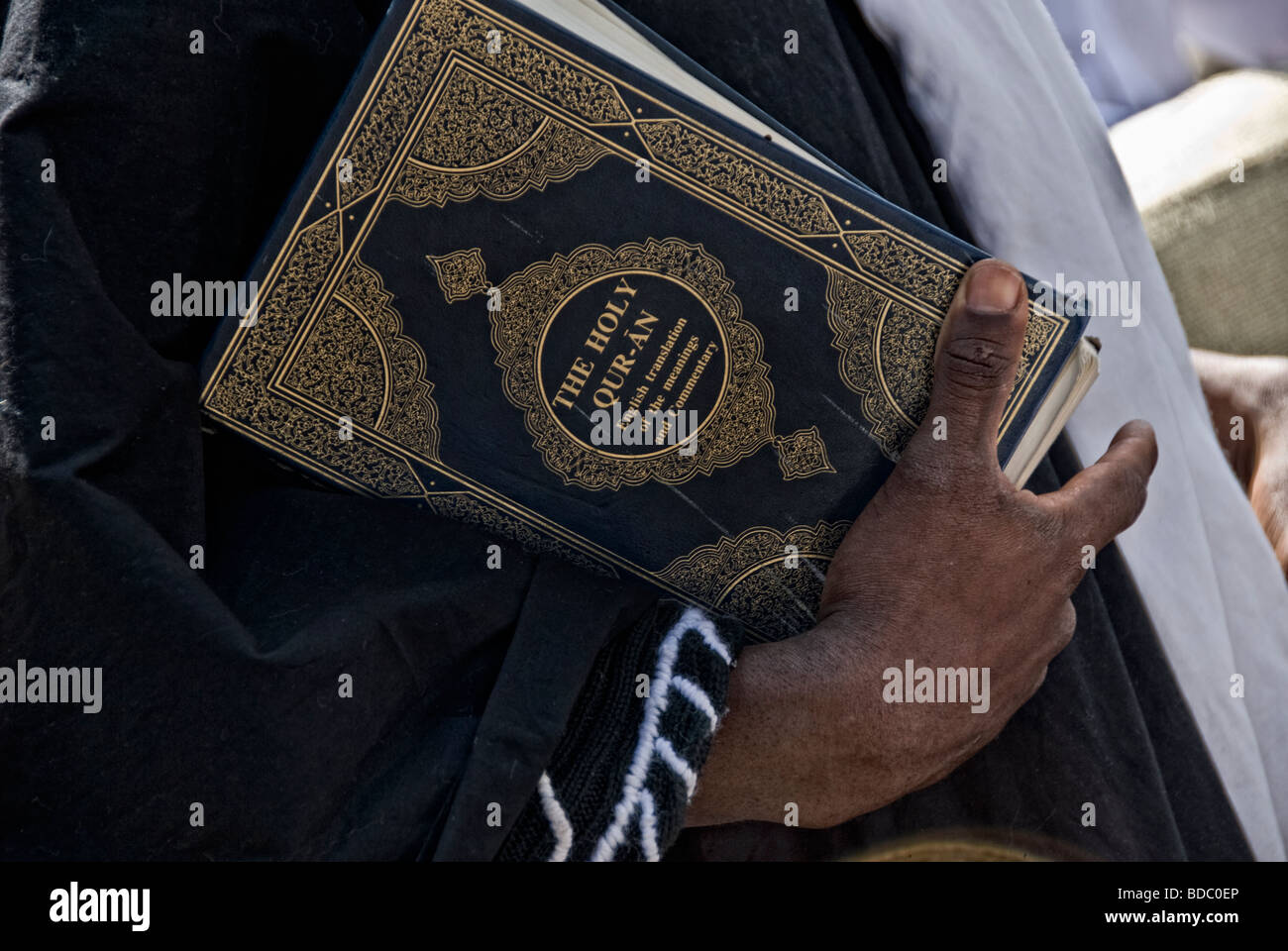 CLOSE UP SHOOT BLACK MAN HOLDING A QURAN - Stock Image
