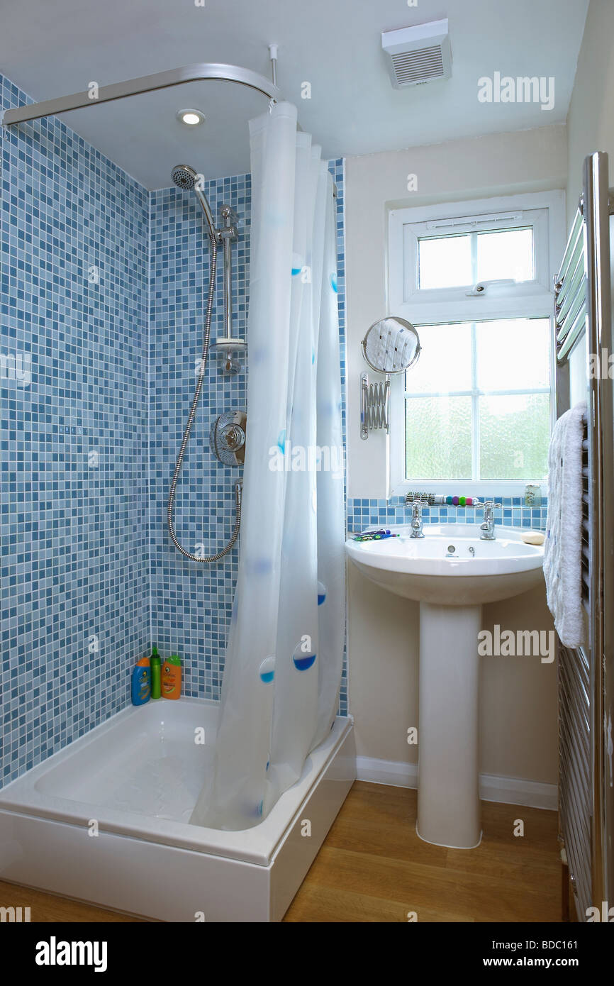 Blue mosaic wall tiles above bath with white shower curtain in Stock ...