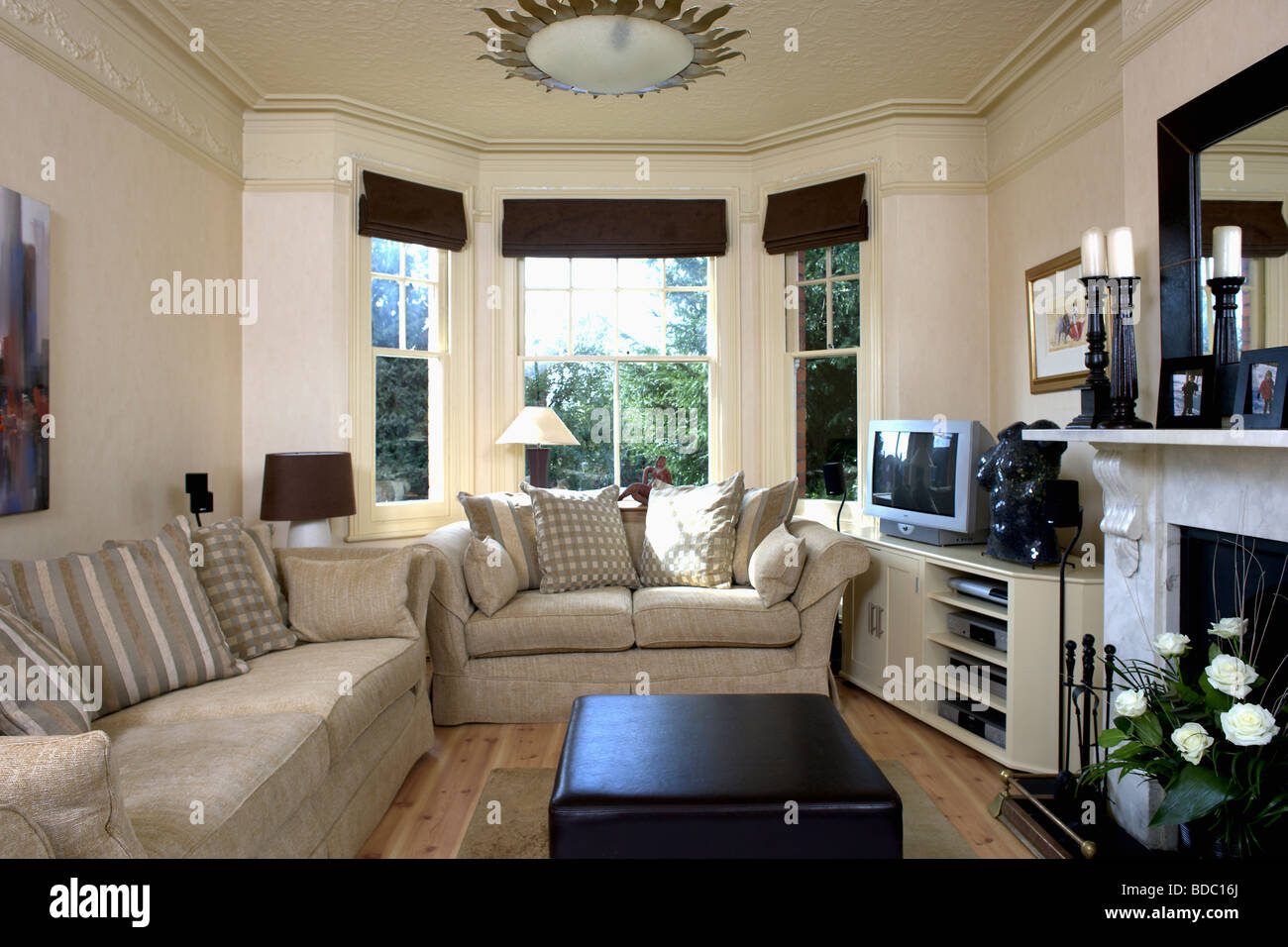Beige sofas in cream living room with black blinds on bay - Living room bay window treatments ...
