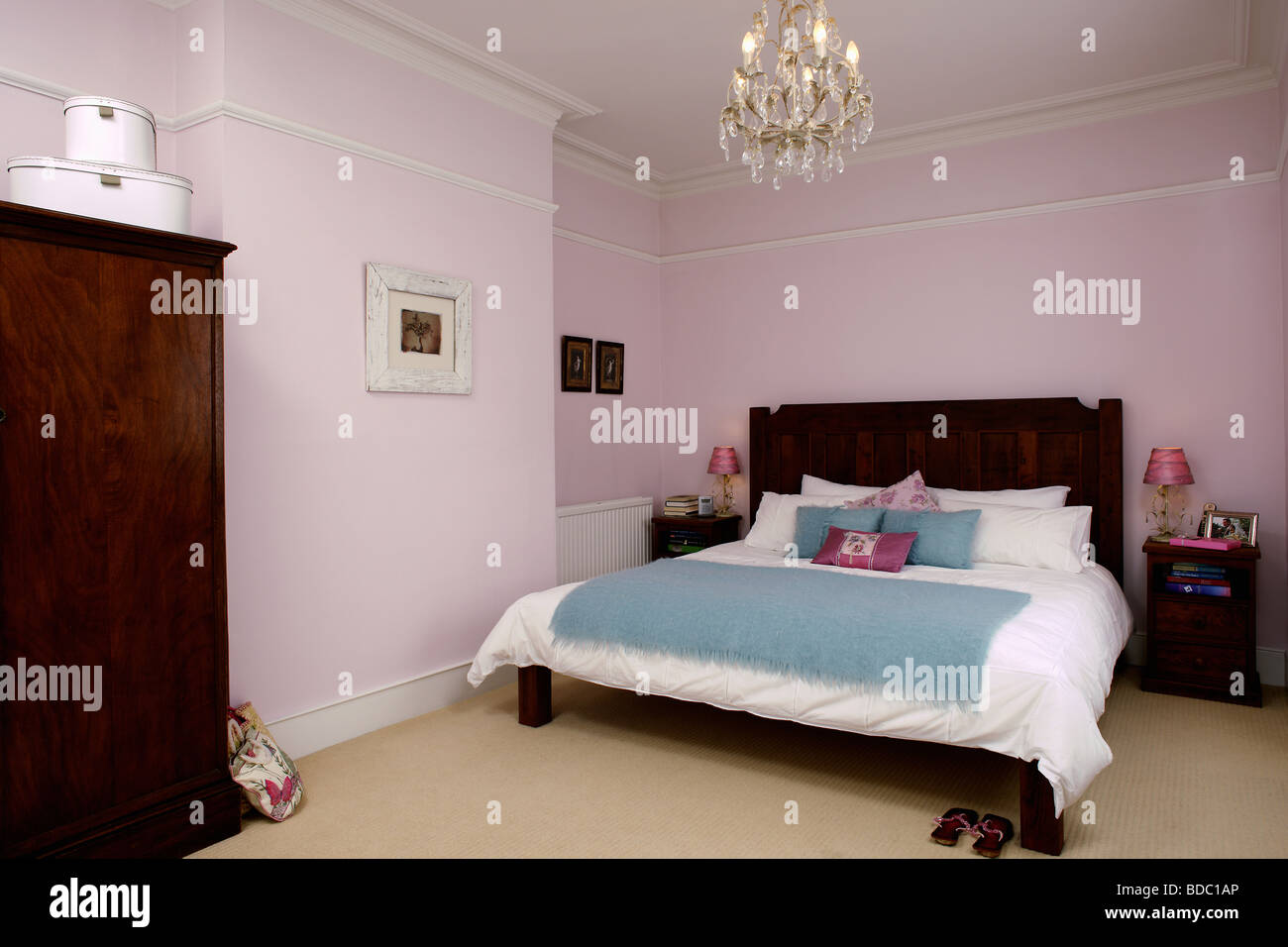 Chandelier above dark wood bed with white bed linen and ...
