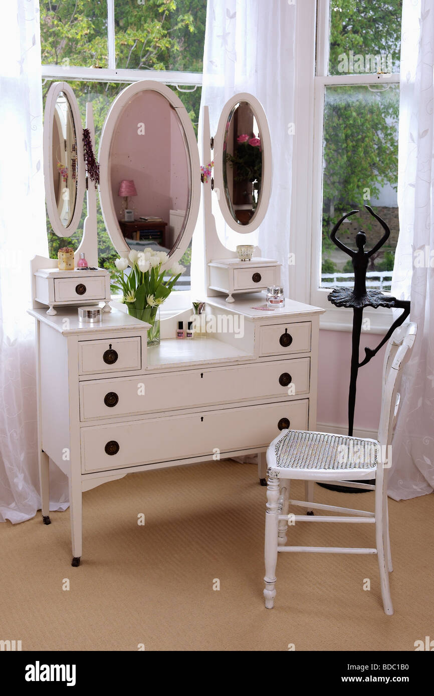 White dressing table with triple mirrors and white chair in front of ...