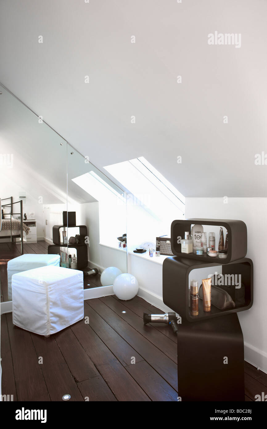 Mirrored wall in white attic bedroom with black wooden flooring and ...