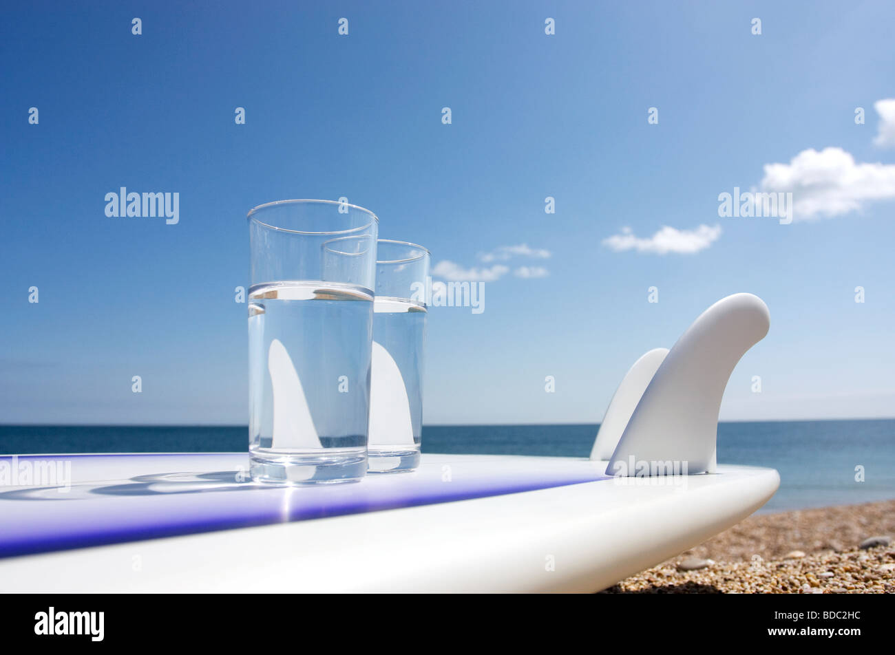Surfboard on beach with two glasses of water Stock Photo