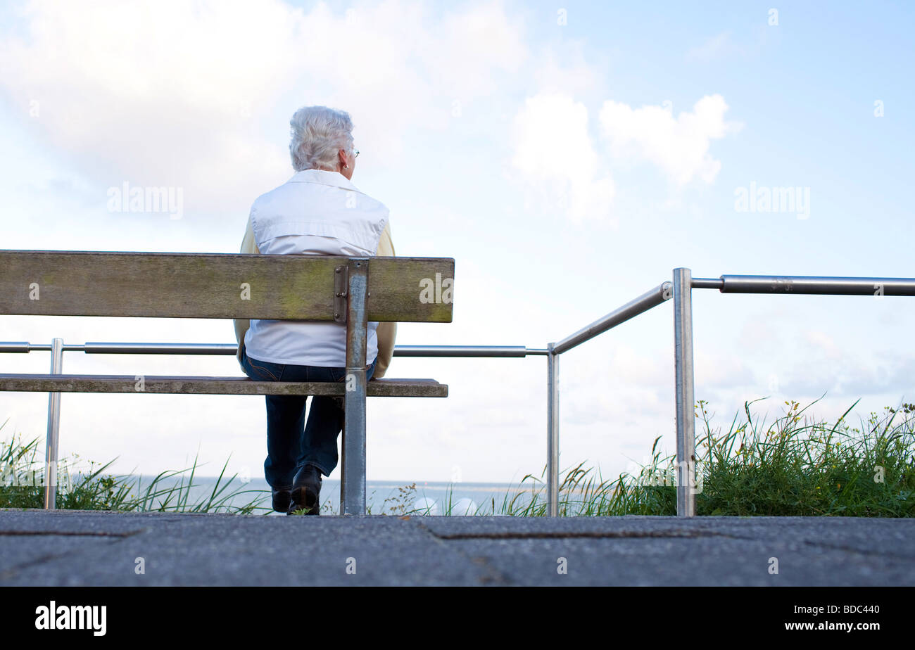 Pensioneer sittin on a BENCH at the Northsea - Stock Image