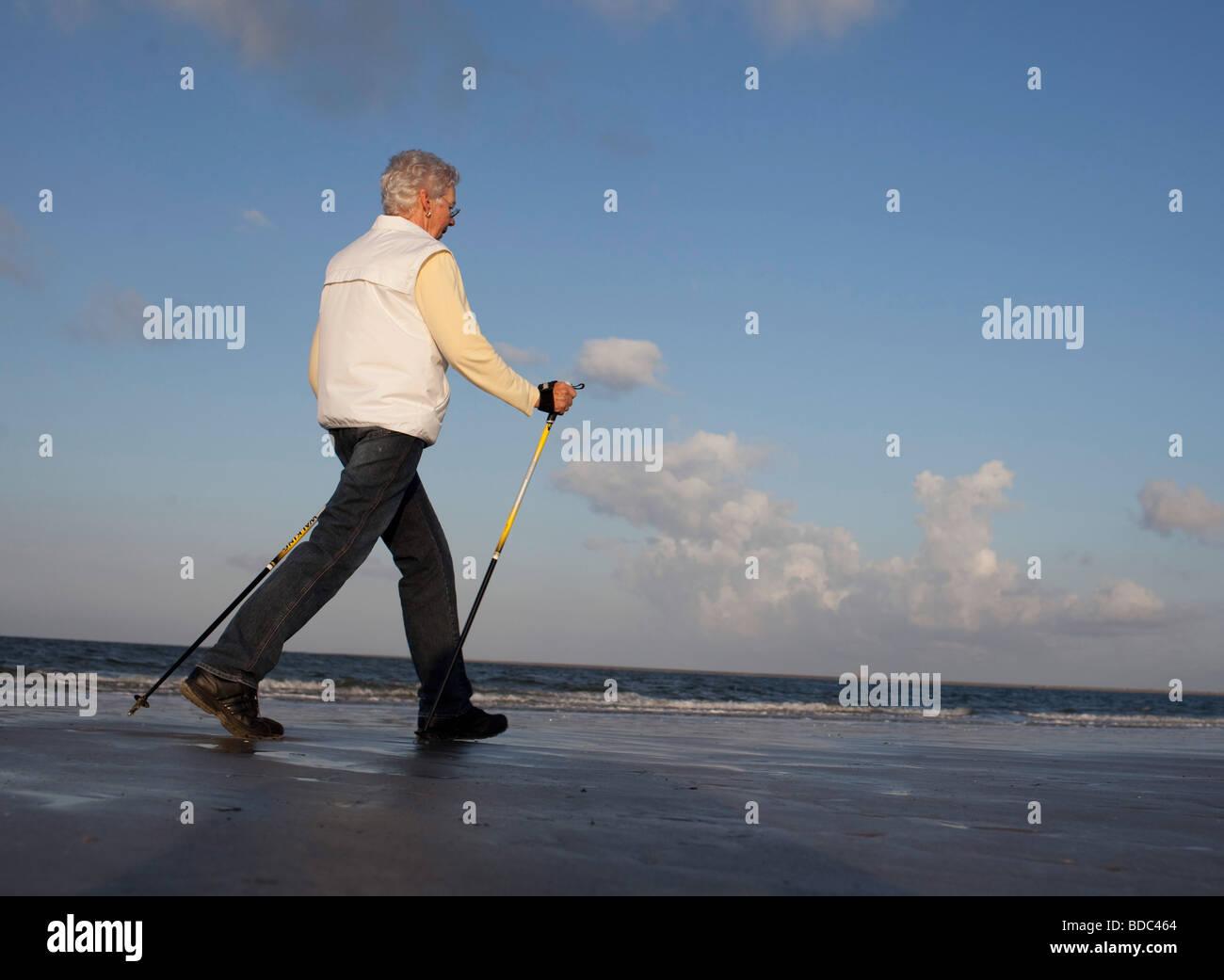 | Woman walking on the beach - Stock Image