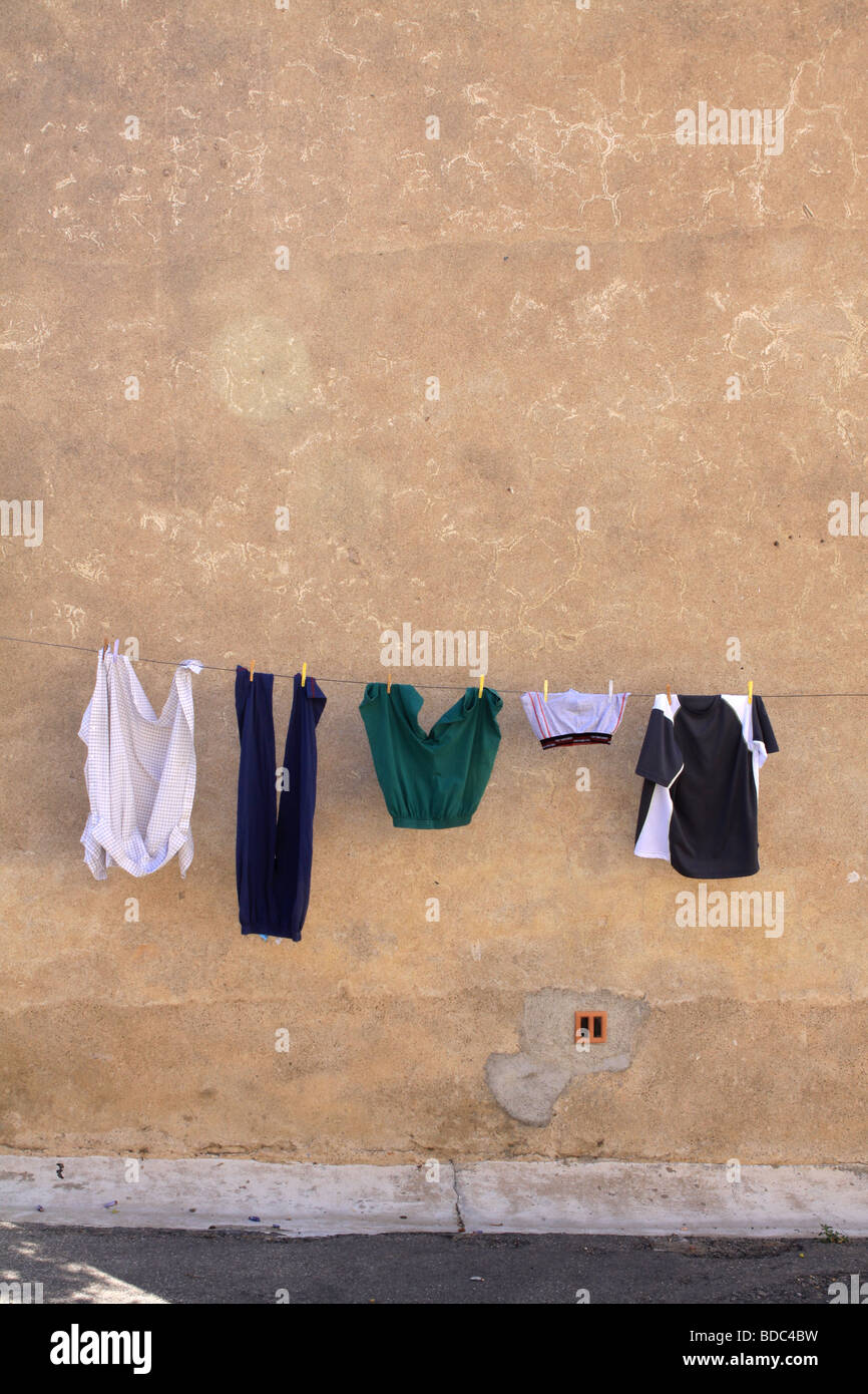 Urban scene of washing hanging in the street for drying against a warm colored wall - Stock Image