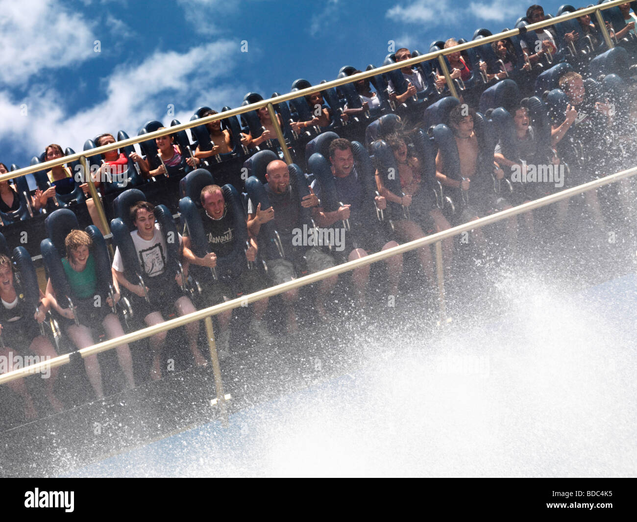 People on Riptide thrill ride descending towards the fountains of water - Stock Image