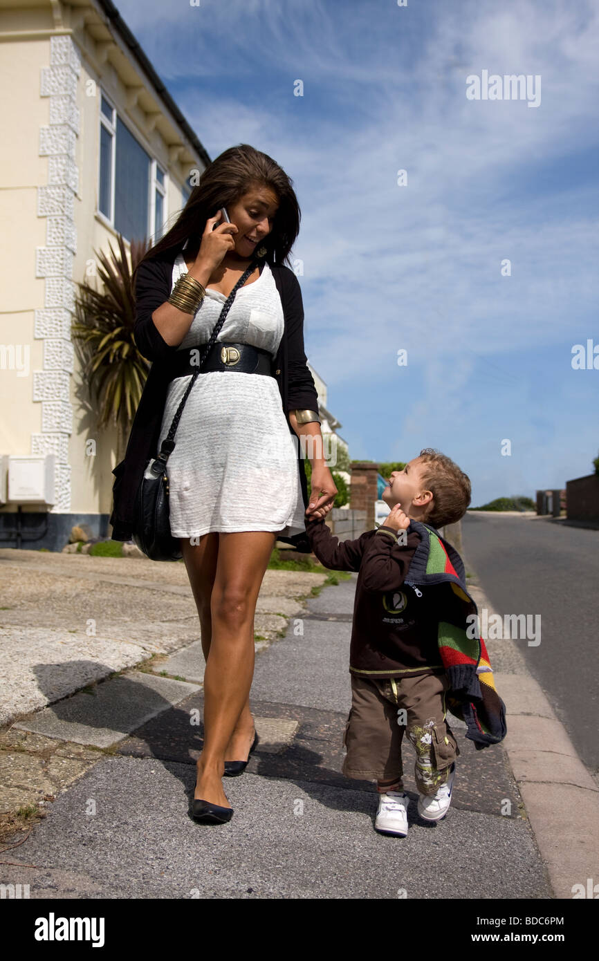 happy young mother on her mobile phone walking down street with toddler boy - Stock Image