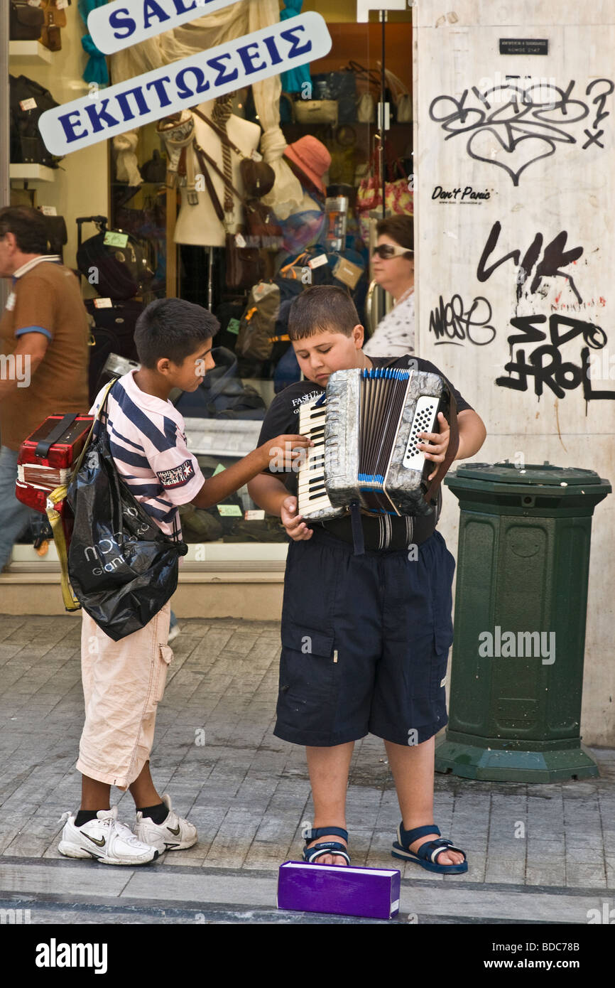 Two young buskers exchange playing tips on Ermou street in the center of Athens Greece - Stock Image