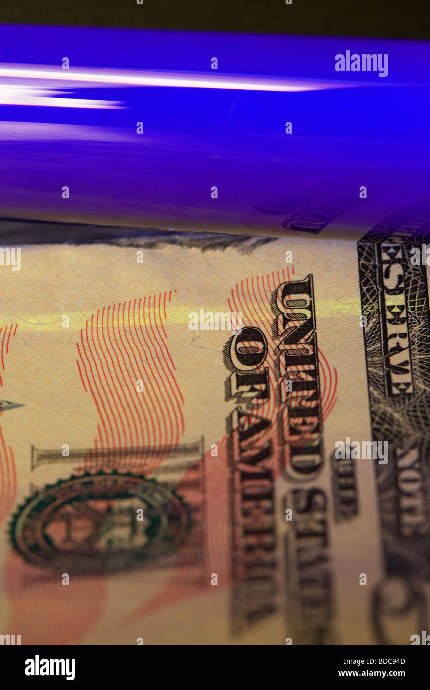 using an ultra violet black light to check a fifty dollar banknote to verify that it is genuine - Stock Image