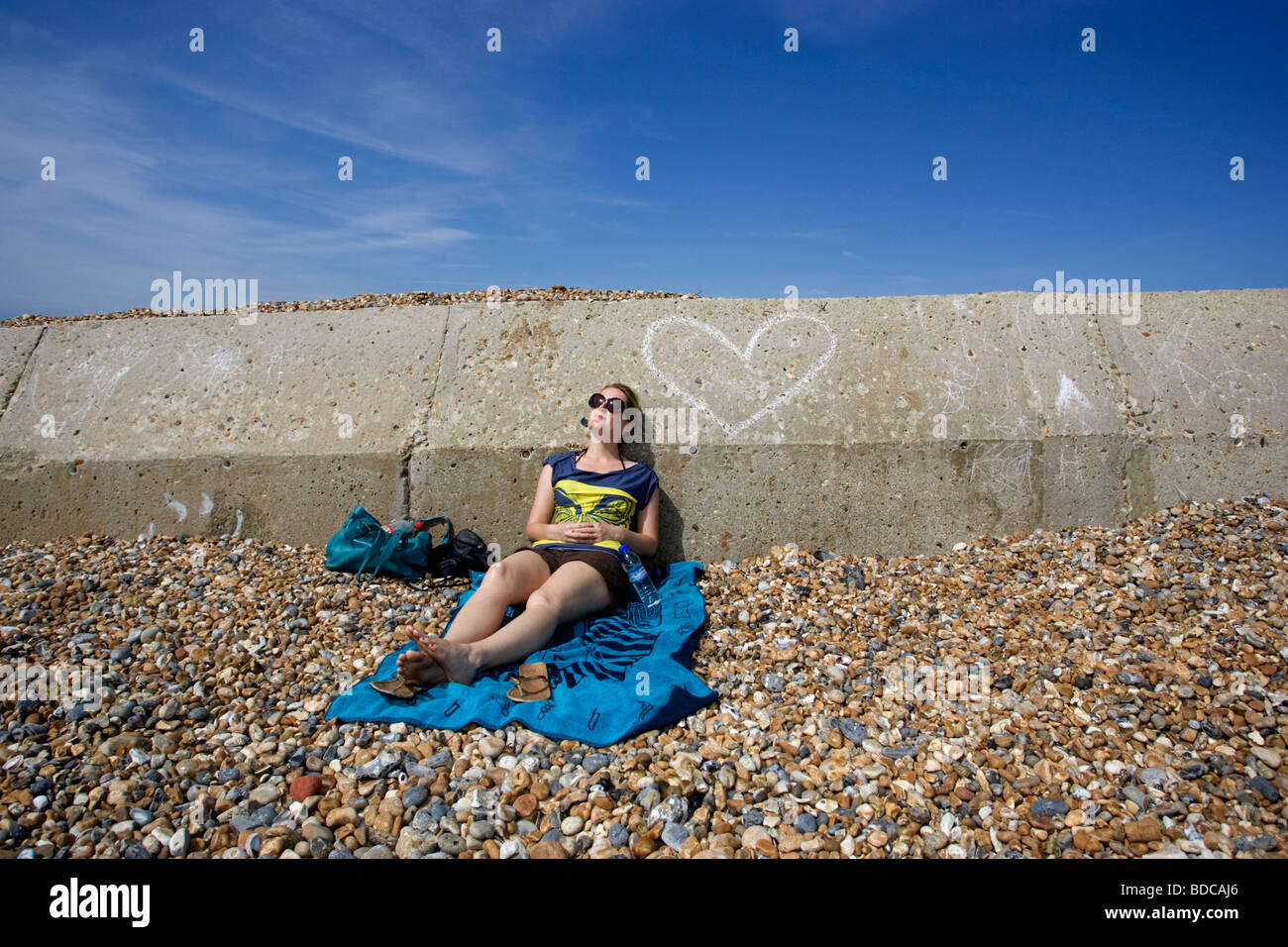 A girl pictured sunbathing on Brighton and Hove's seafront beach in hot weather, East Sussex, UK. - Stock Image