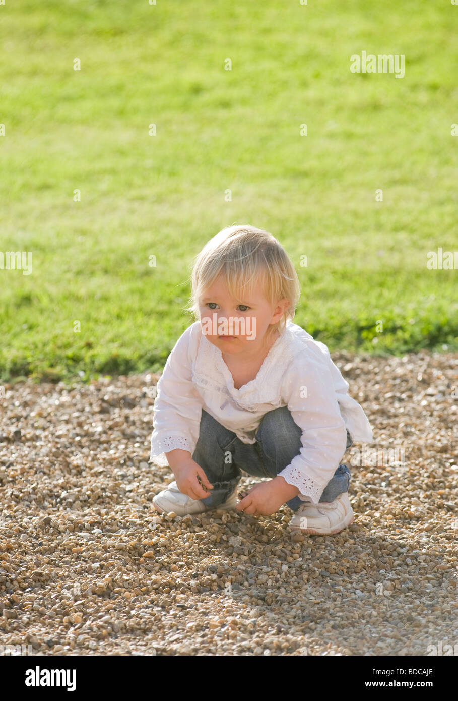 Baby girl 21 months old, on gravel path, - Stock Image