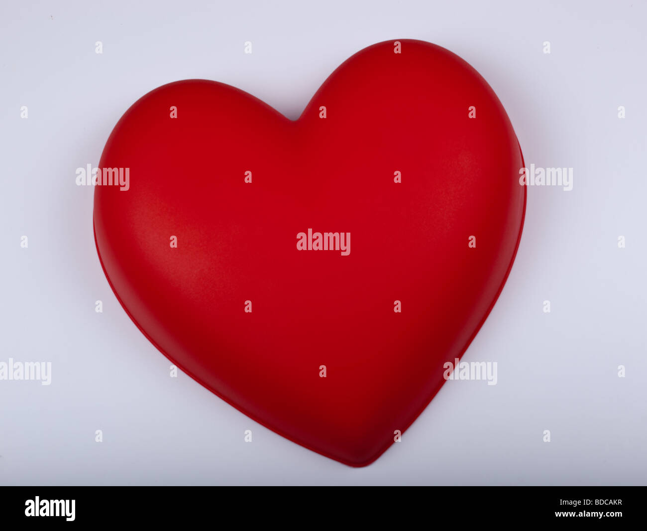 Red plastic heart lies on a white plastic background - Stock Image