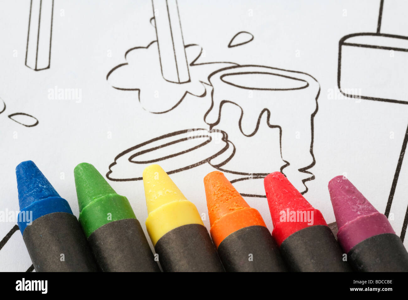 Wax coloured crayons on children's line drawing for colouring in a sketch pad - Stock Image