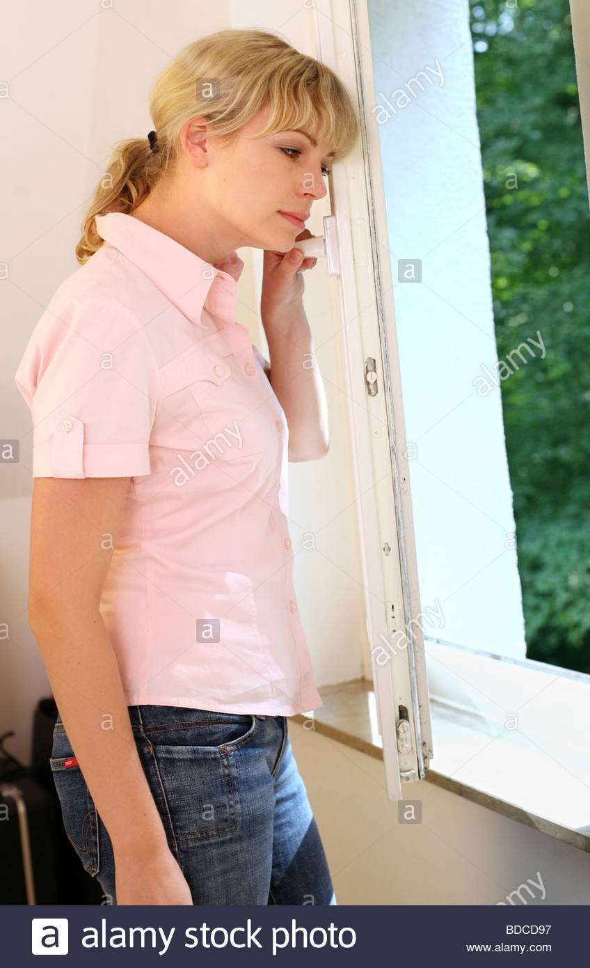 woman standing in front of a window - Stock Image