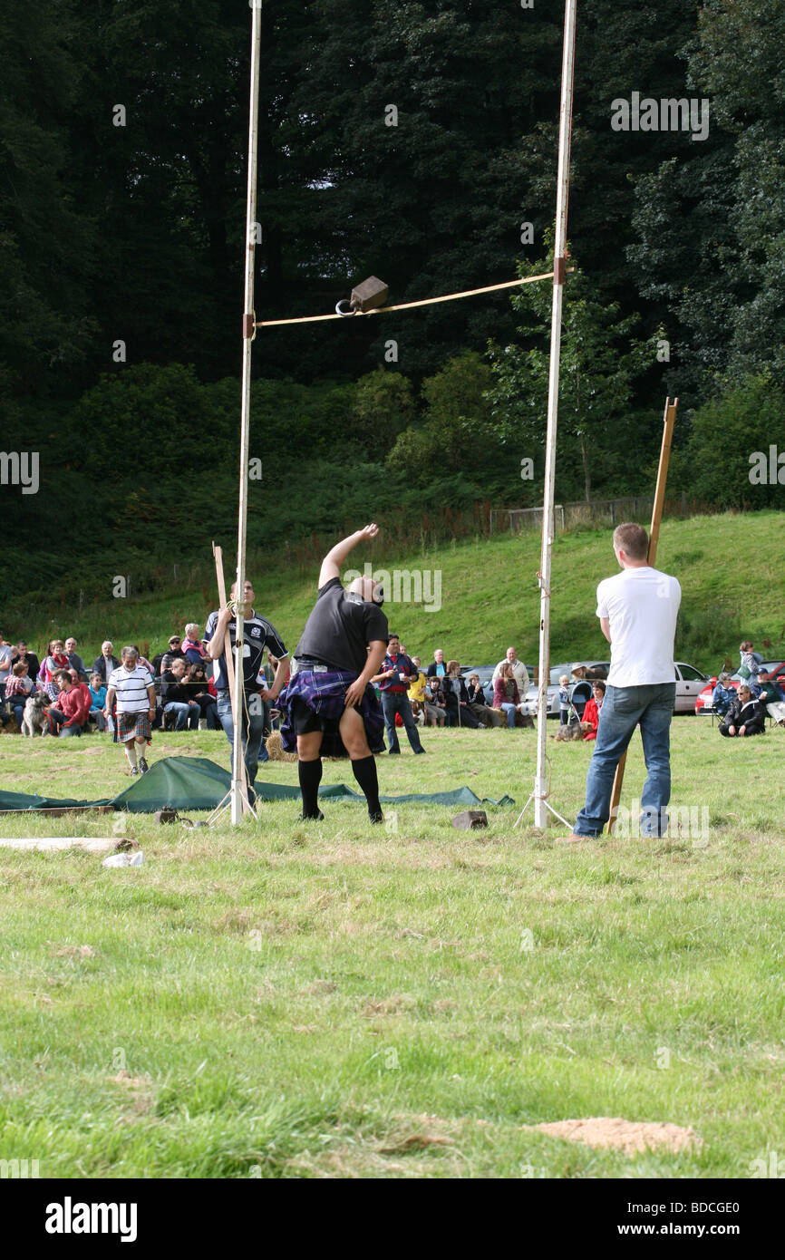 man competing in weight over bar at Cortachy 2009 highland games Scotland  August 2009 - Stock Image