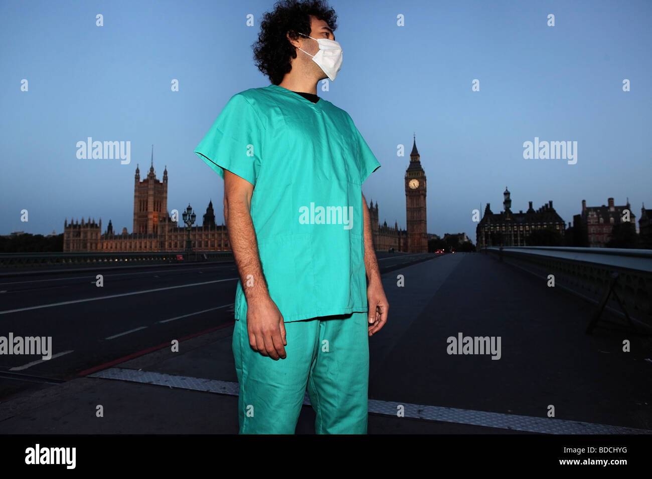 Young man with surgical face mask and jade uniform looks lost nearby the Big Ben, on Parliament Bridge, London. - Stock Image