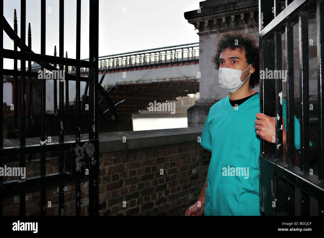 Young man with a surgical face mask looks scared nearby the Blackfriars Bridge in London. - Stock Image