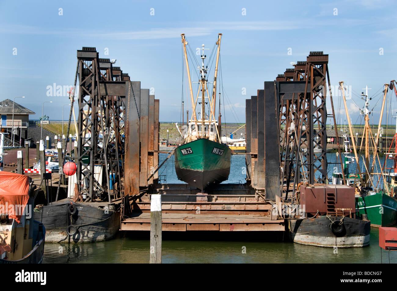 Oudeschild Texel Netherlands fishing trawler floating dry dock shipyard port harbor Wadden Sea Waddenzee Wad - Stock Image