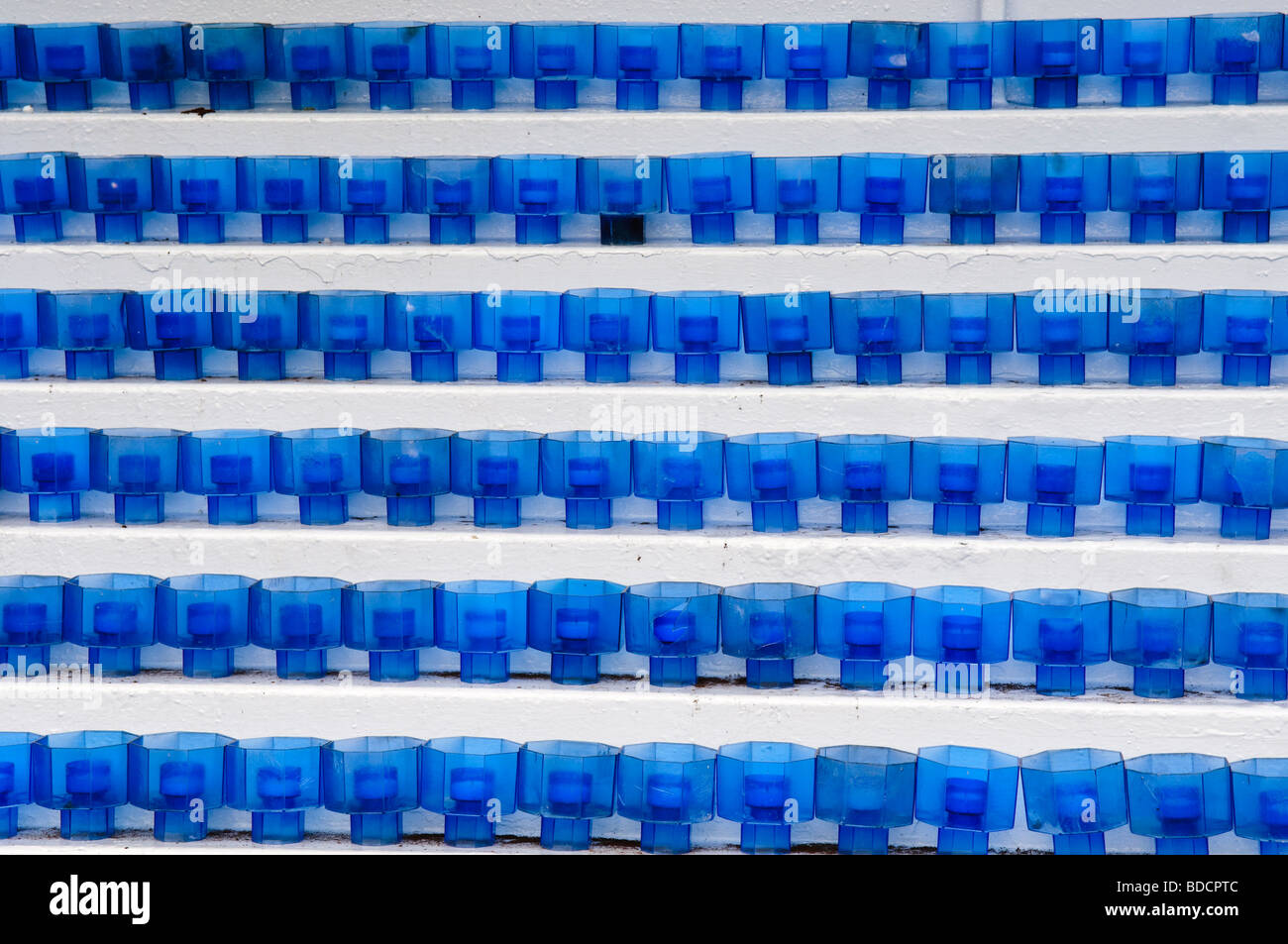Rows of blue candle holders on shelves in a modern church - Stock Image
