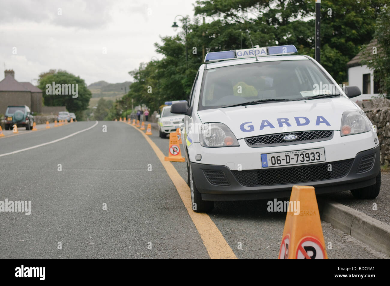 Two Irish Garda police cars parked on a no parking zone with no-parking traffic cones. - Stock Image