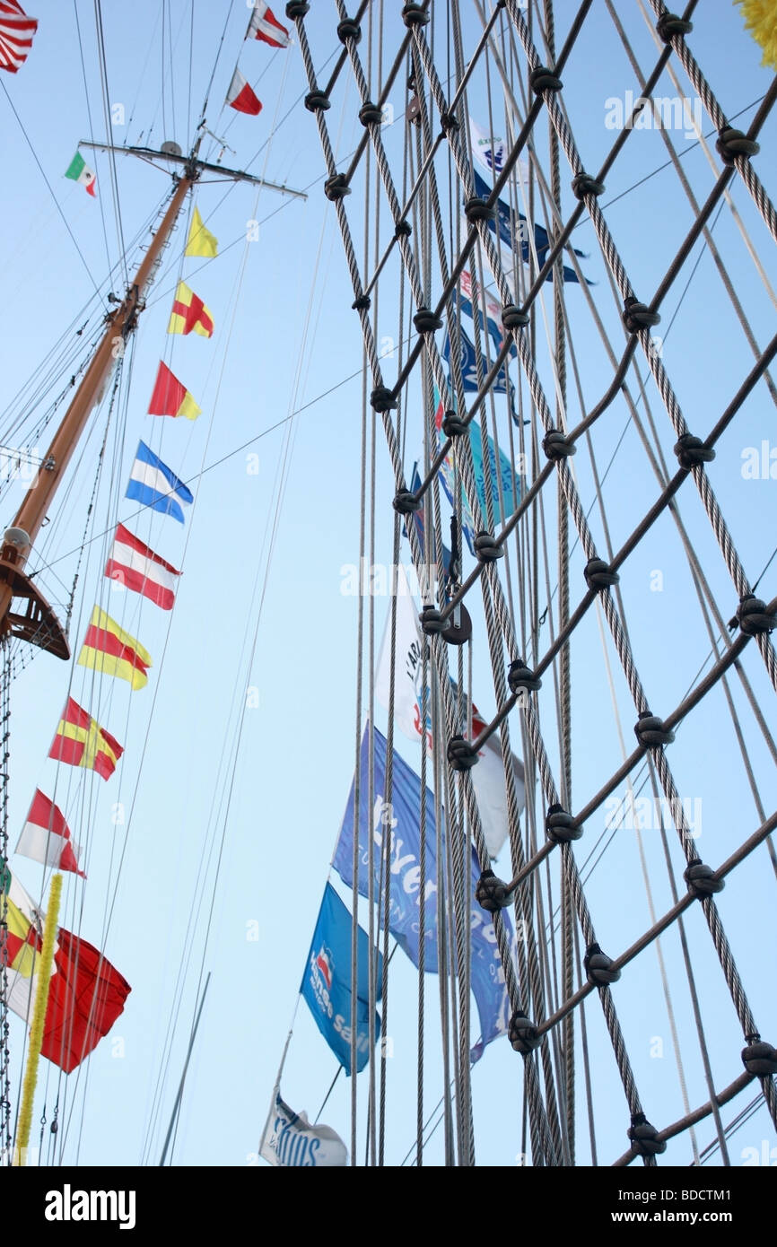 flag mast pulley rope sail ship sky vessel white - Stock Image