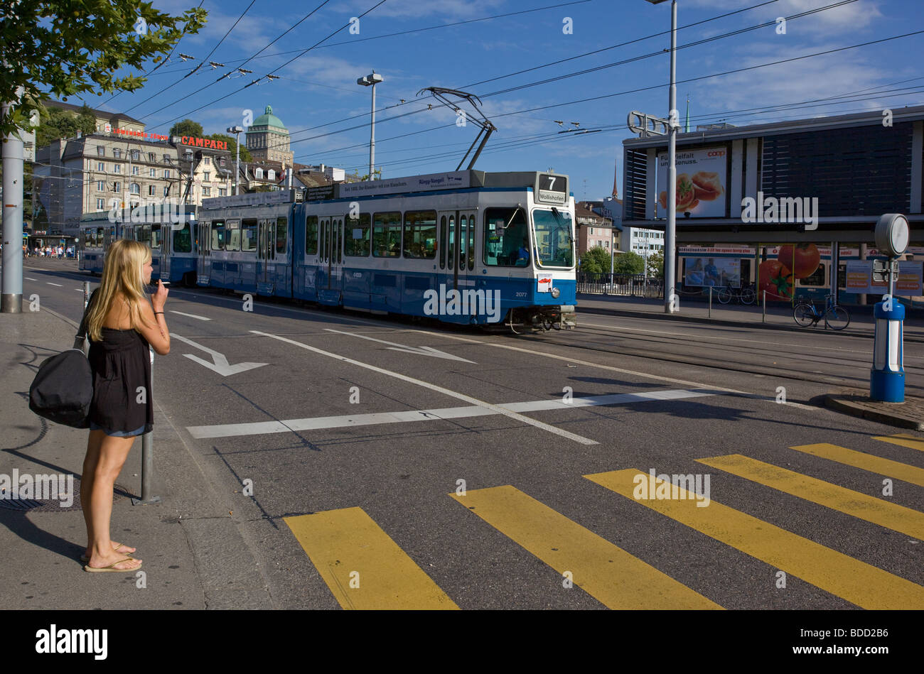 Smoking woman looking for passing Trams before crossing the street Zurich Switzerland - Stock Image