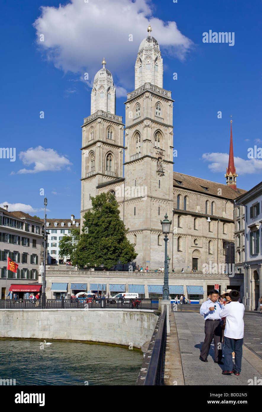 Asian tourists taking pictures in front of Zurich Fraumünster cathedral - Stock Image