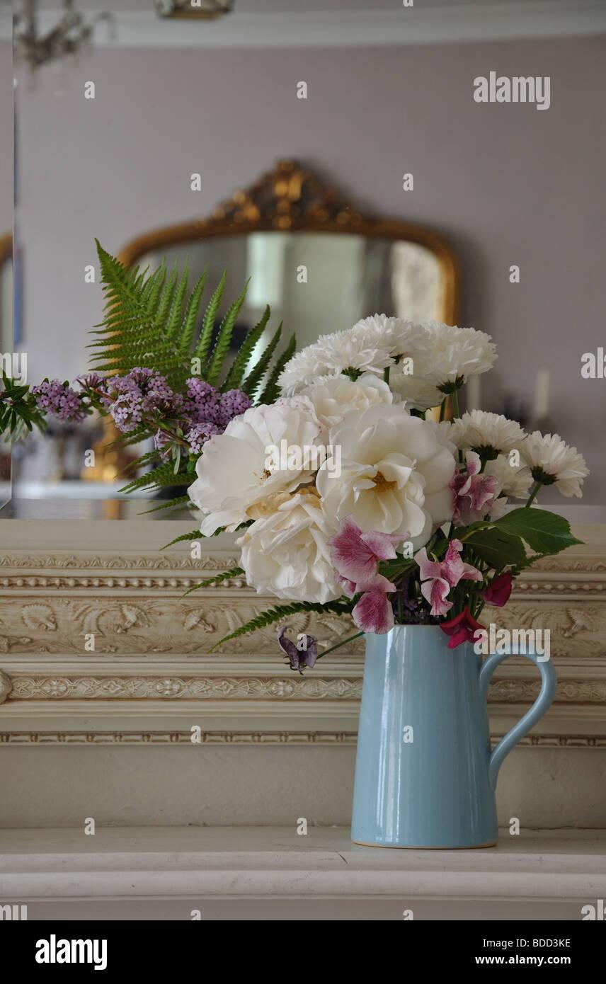 Jug of flower against ornate mirror - Stock Image