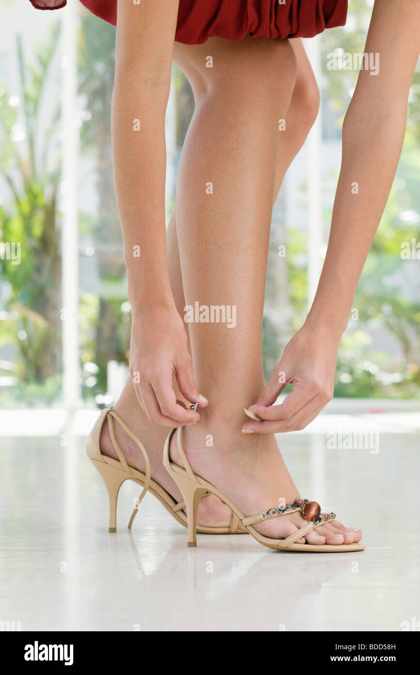 Woman putting on high heels - Stock Image