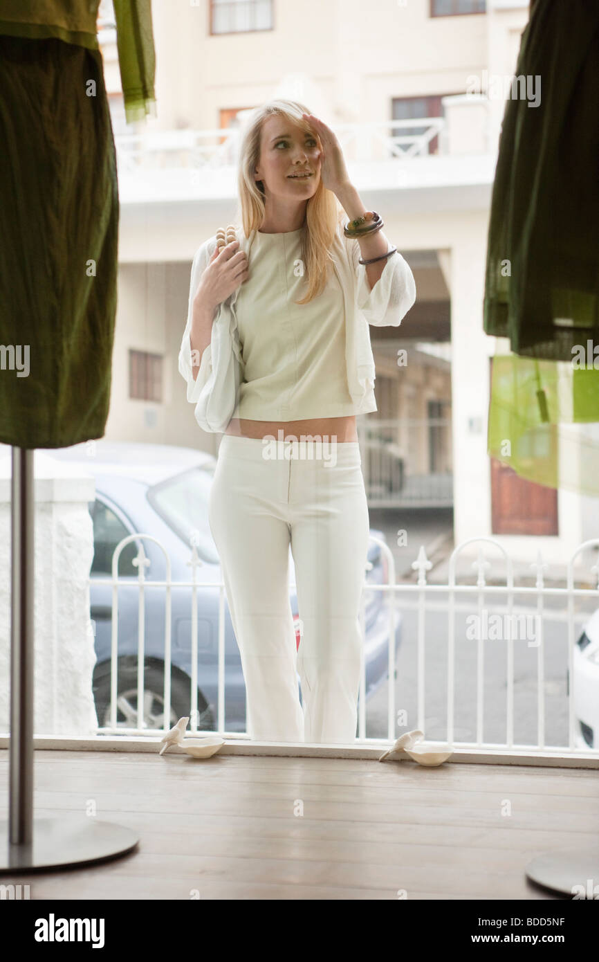 Woman window shopping in a boutique - Stock Image