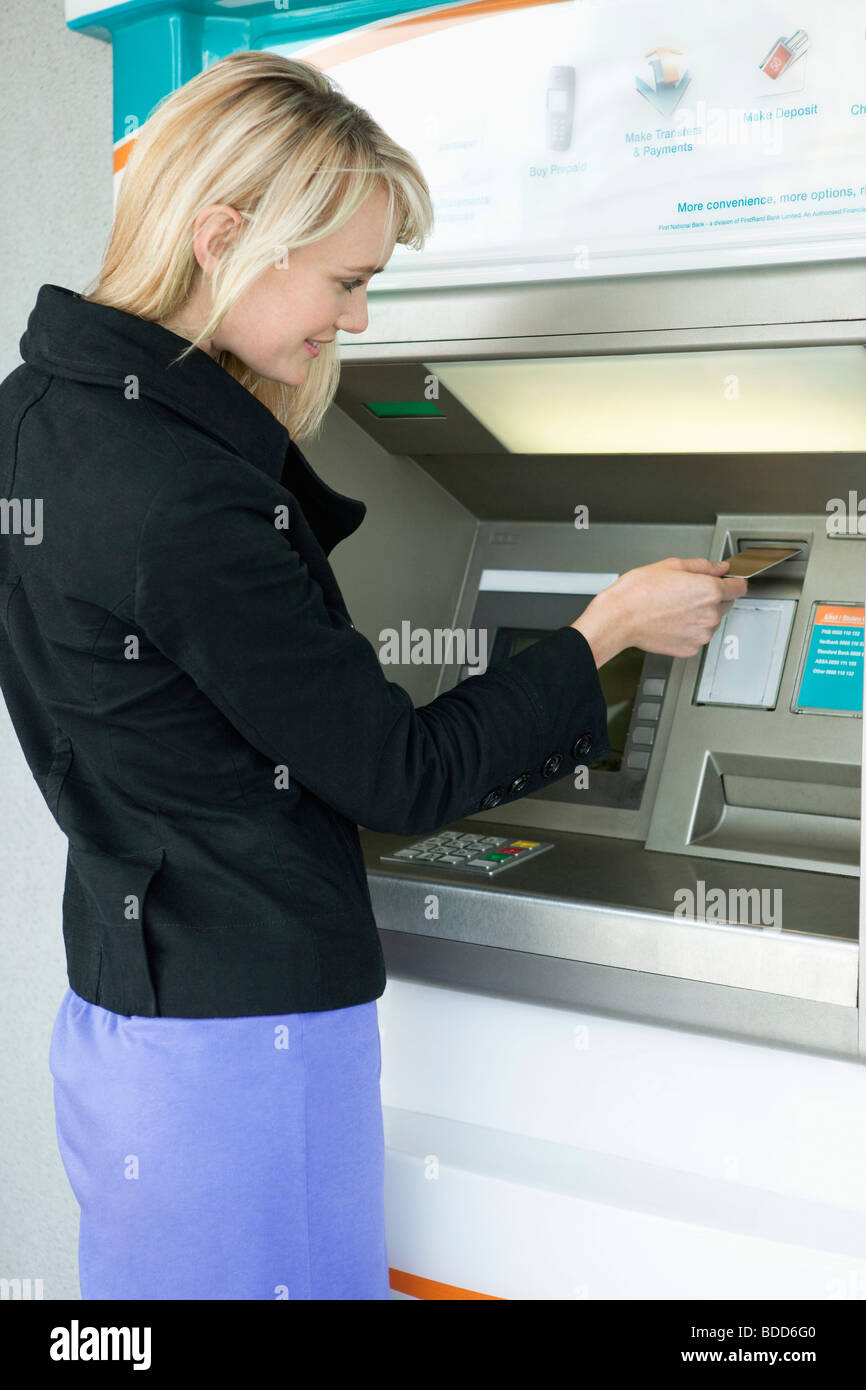 Woman inserting a credit card into ATM - Stock Image