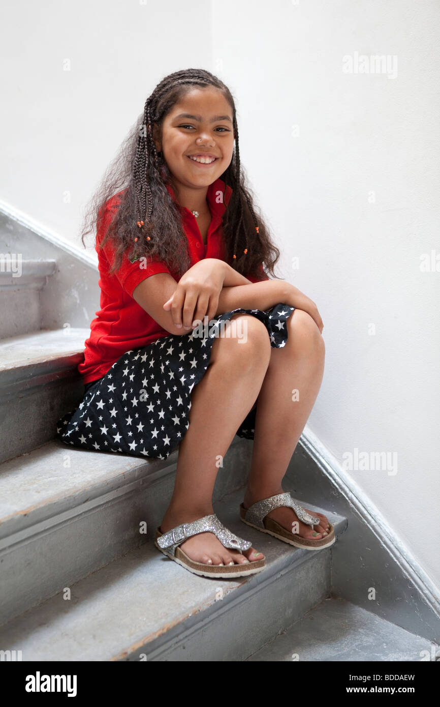 Happy little girl sitting on the stairs - Stock Image