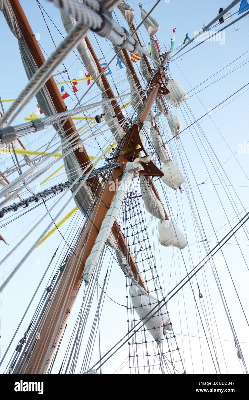 Mast with white sails and flags of the world - Stock Image