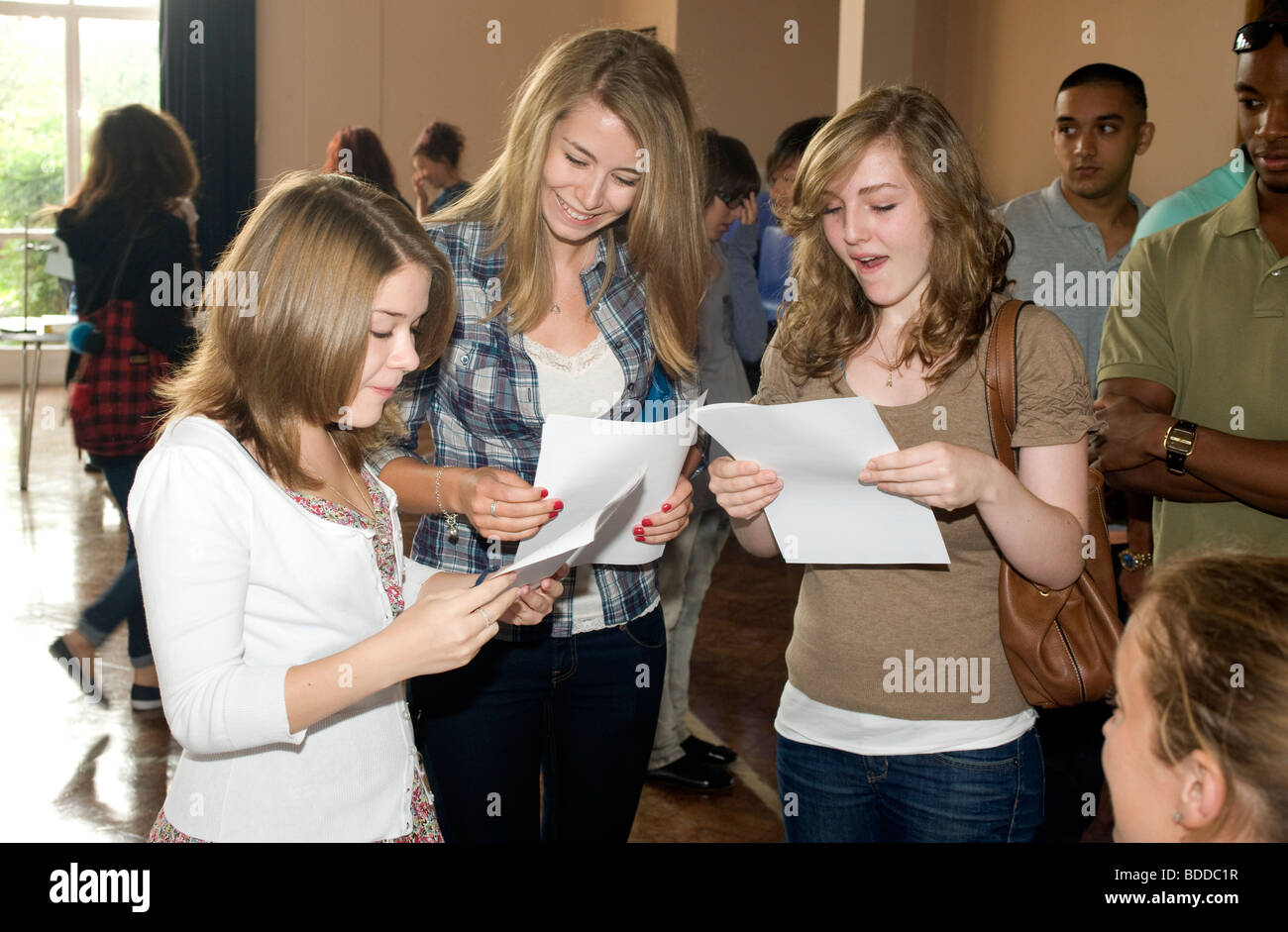 Three teenage girls looking happy with their GCSE A Level exam results - Stock Image
