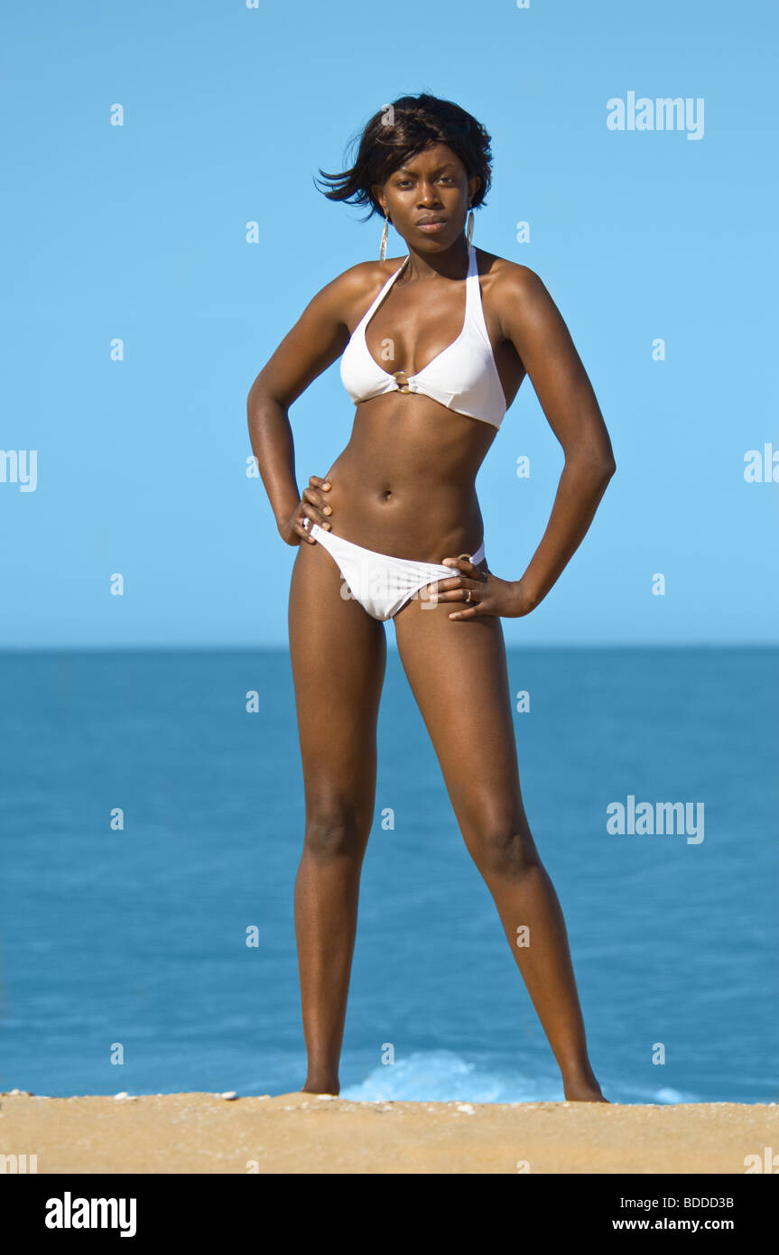 A slim attractive young African woman posing on a golden sandy beach with a blue sea and sky in the background. Stock Photo