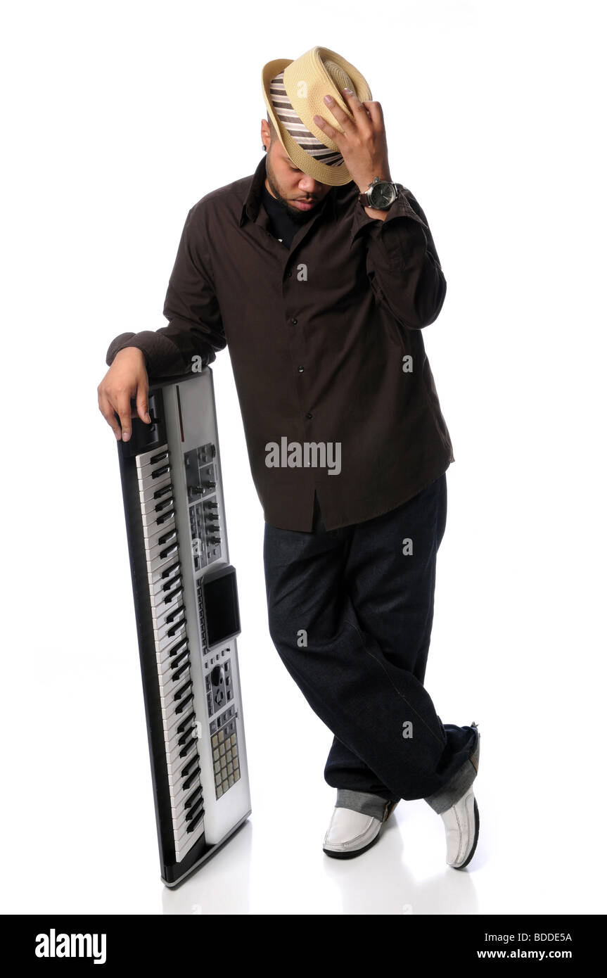 Young African American man posing alongside electric piano - Stock Image