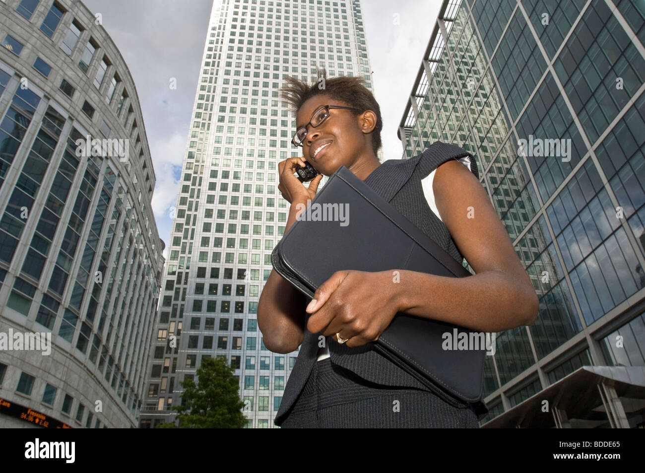 An attractive African business woman talking on her mobile phone at Canary Wharf with modern office buildings in - Stock Image