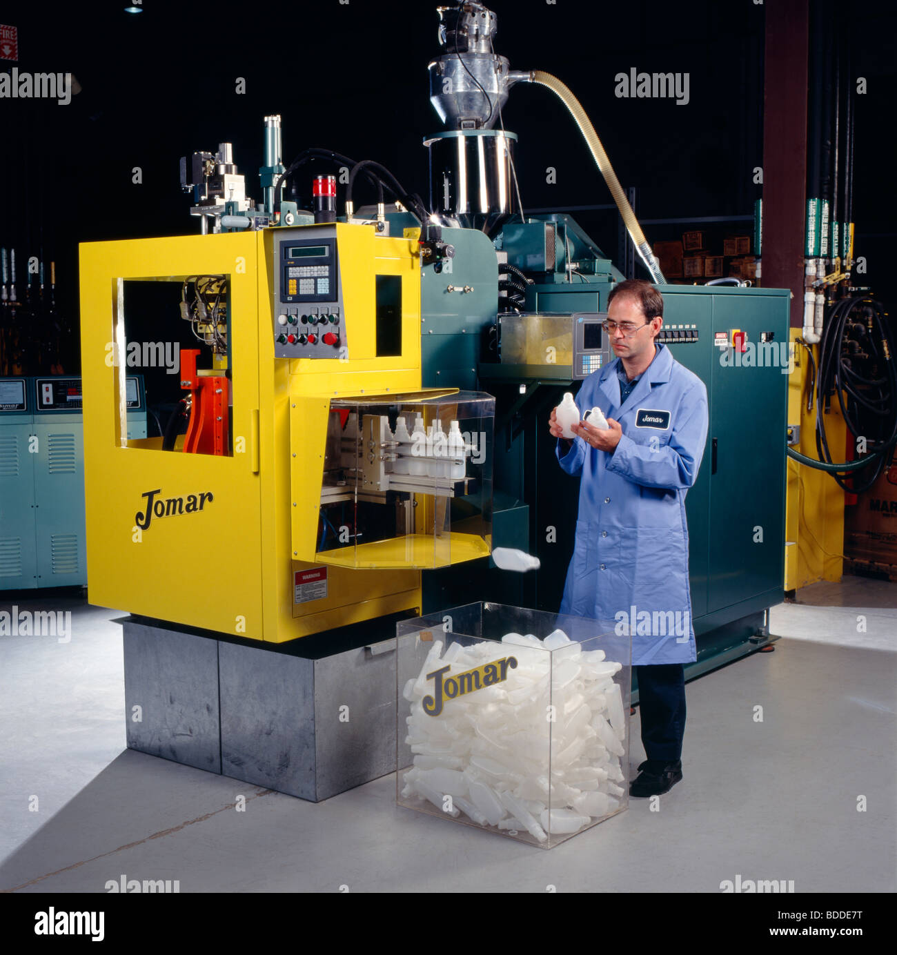 Extrusion blow molding machinery makes plastic containers. - Stock Image