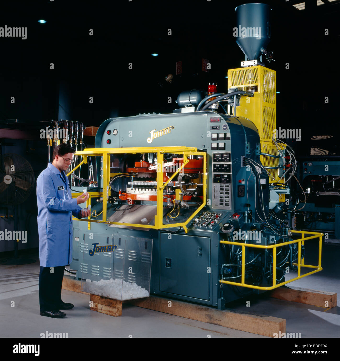 Injection blow molding machinery makes plastic containers. - Stock Image