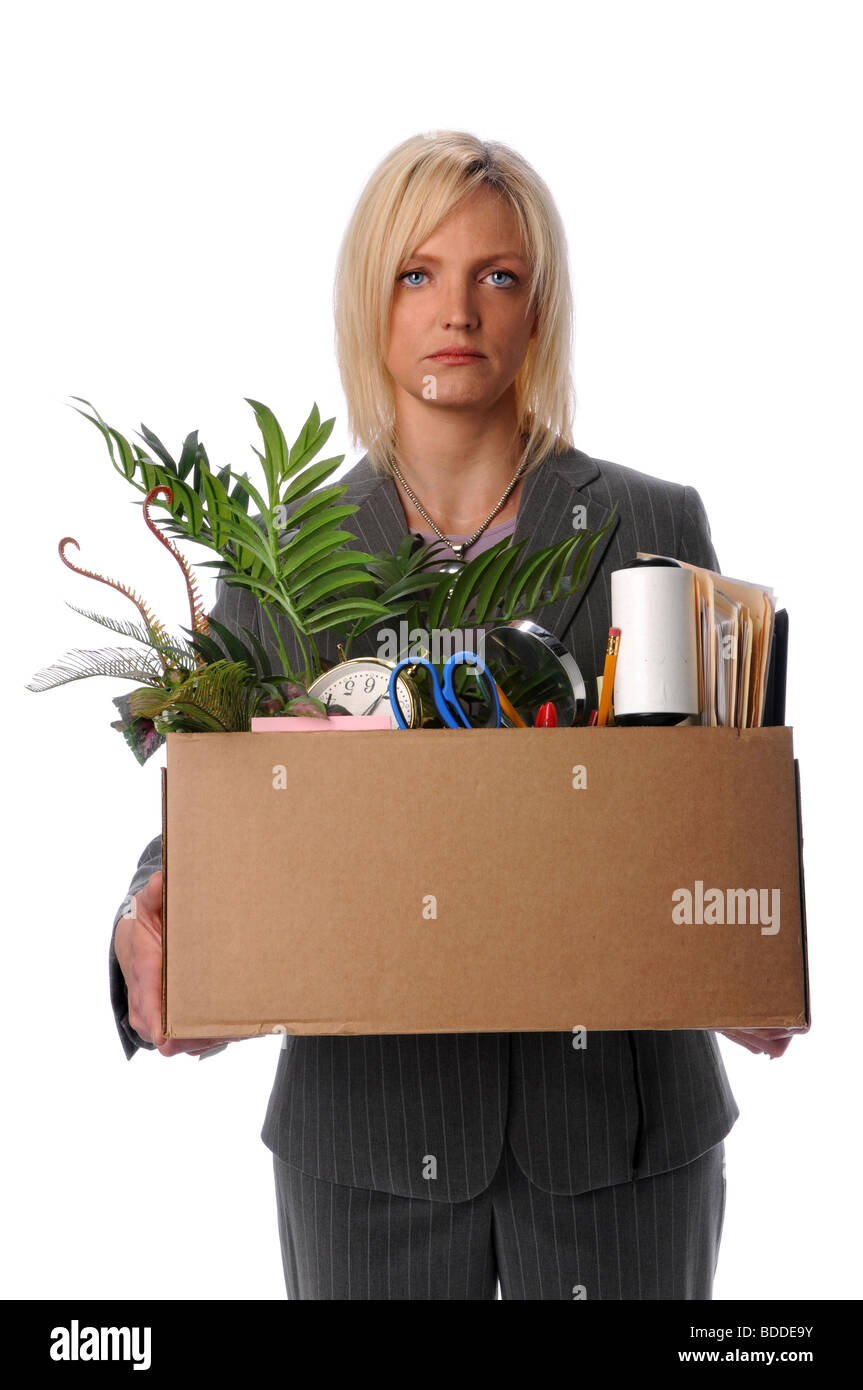Sad businesswoman carrying belongings in box after loosing job - Stock Image