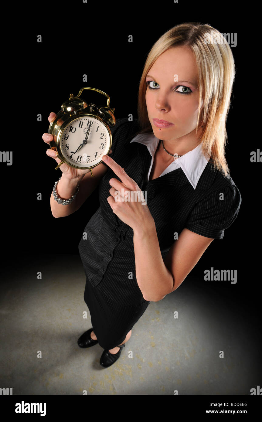 Attractive businesswoman pointing at alarm clock - Stock Image