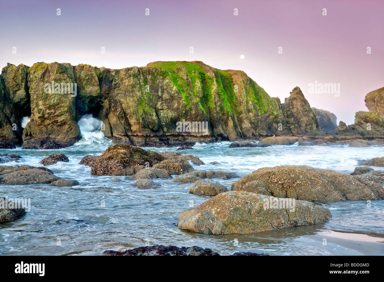 Rocks, moon, low tide and wave at Bandon beach. Oregon - Stock Image