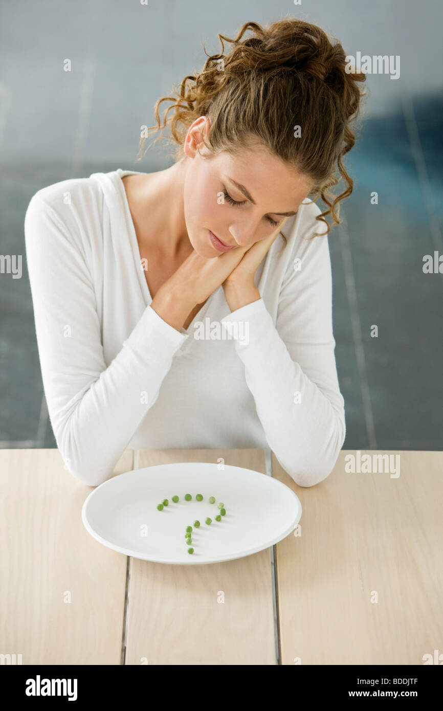 Woman sitting at a table with peas in question mark shape on a plate - Stock Image