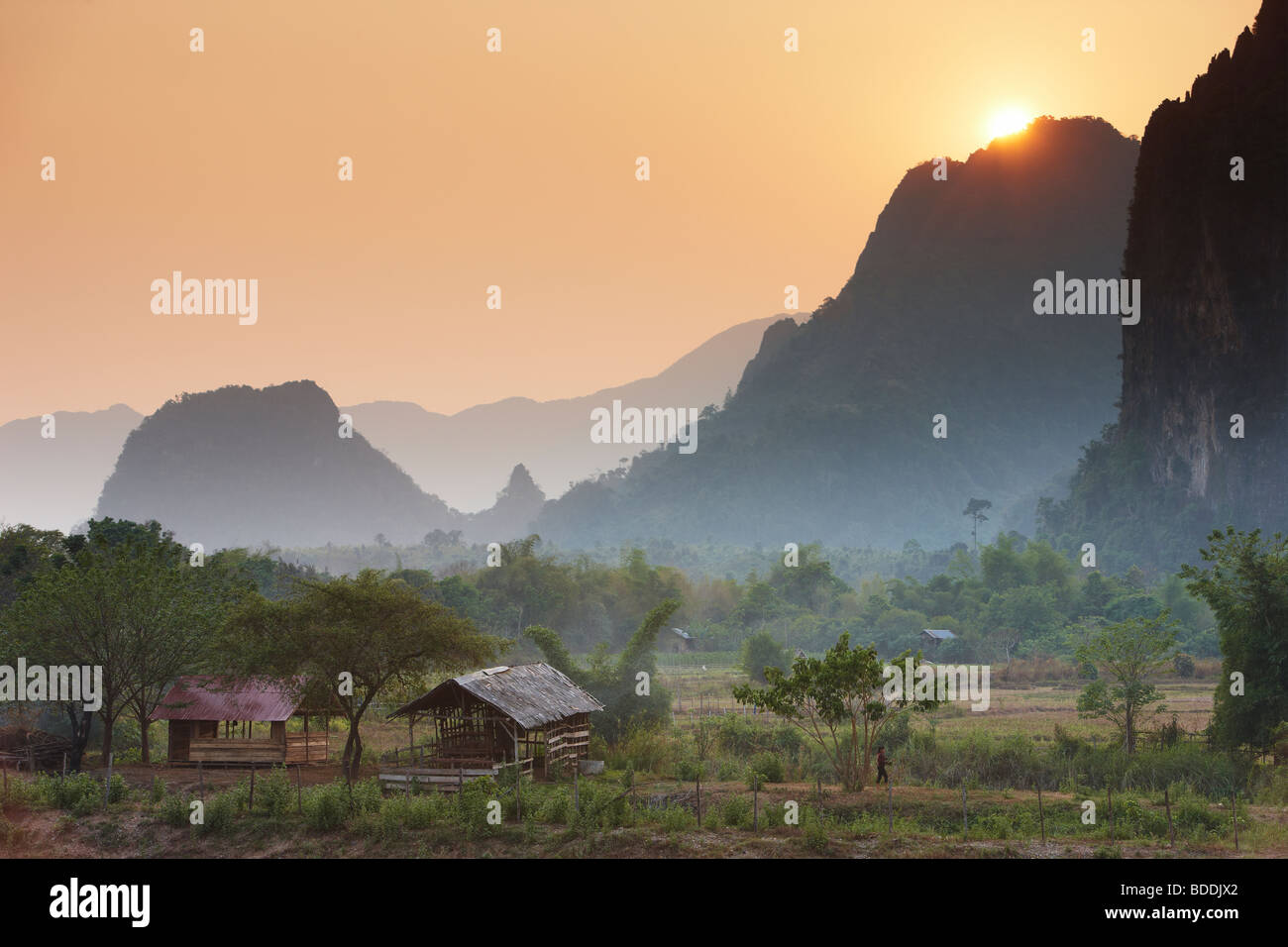 the sun dissappearing over the mountains nr Vang Vieng, Laos - Stock Image