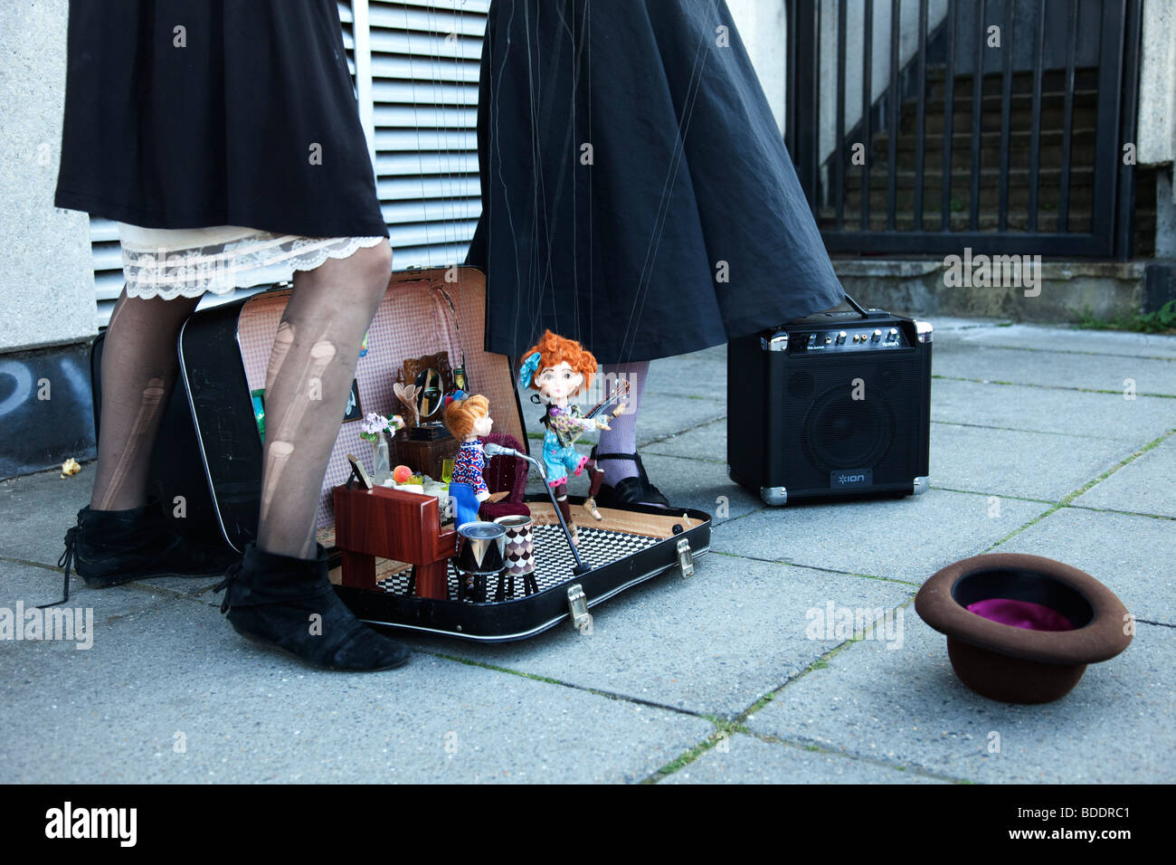 Two female puppeteers operate their puppet show on the Southbank. The puppets perform in a garage rock band. London. - Stock Image
