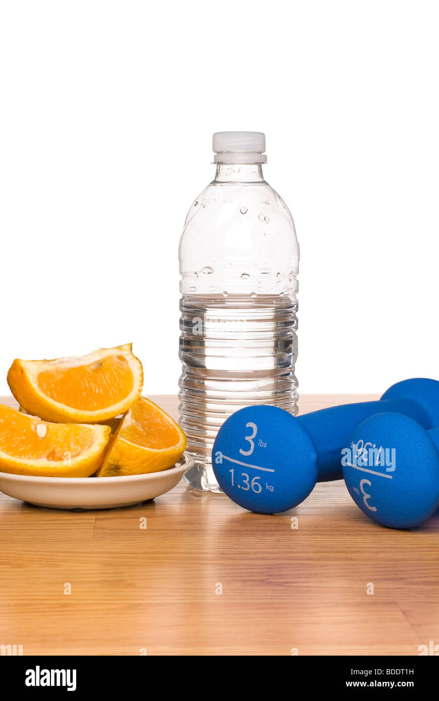 A conceptual image of healthy living including exercise equipment, a bottle of water and a sliced orange. - Stock Image